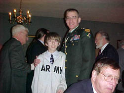 "Son Joshua stands with Dad, Chaplain and Past President LTC Peter K. Goebel. Member James ""Jim"" T. Hays is in right rear of the picture and long time SAR member (12/19/1969) Noel Haskell is pictured in the foreground.  Joshua led the Pledge of Allegiance for us at the start of the meeting  - Thank you Joshua."