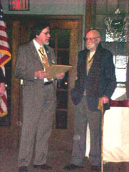 Dennis Marr presents Carl Covell with a letter outlining Carl's faithful and long-time service to the Chapter.  Carl received an enrollment in the National Society's Life Membership Program for his service to the chapter and in honor of his upcoming 90th birthday on February 26, 2003.