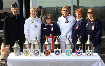 The Gold Star and Blue Star mothers along with an American Legion member standing with the lighted lanterns